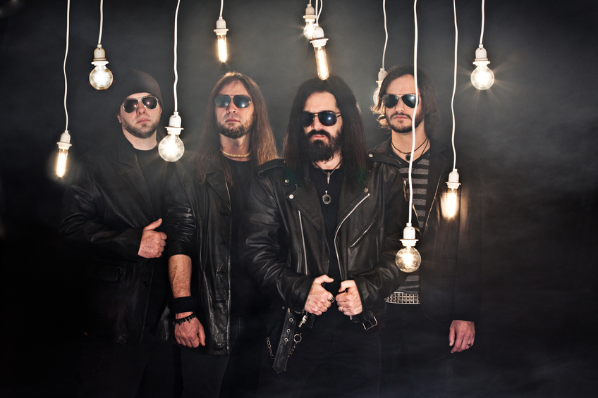 A promo photo of a heavy metal band surrounded by hanging light bulbs.